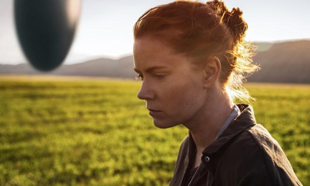 Amy Adams schaut nachdenklich während das außerirdische Raumschiff unweit über dem grasgrünen Boden hängt