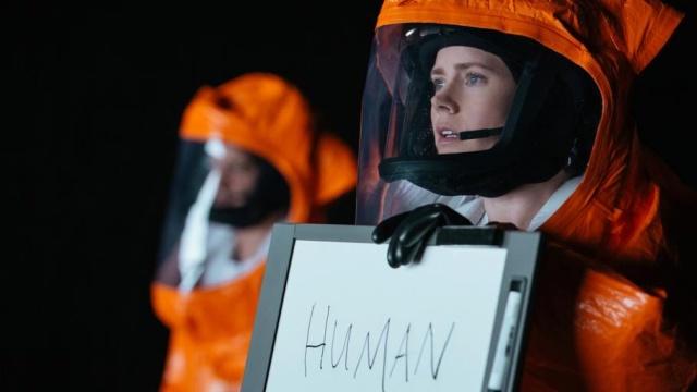 "Amy Adams trägt knallorangen Schutzangzug und hält Tafel mit dem Wort ""human"" (Mensch) in der Hand"